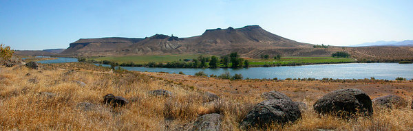 Stock image of a panorama of the Idaho landscape on the Snake River south of Boise, Idaho USA with Bonneville melon gravels iin the foreground and a large mesa in the background.  The melon gravels and river basin were shaped by the flood from Lake Bonneville about 15,000 years ago.  Lake Bonneville was located in what is now known as Salt Lake. The flood occurred when a natural alluvial deposit acting as a dam failed, and water from the lake flowed north and west into the Snake River Plain and Snake River Canyon. This flood carved the Snake River Canyon deeper and deposited sediments and debris along the way. The basalt boulders were deposited by the Bonneville Flood and are called melon gravels because the size and shape of the boulders are similar to melons.  **Note: Due to the odd size of this image it is not offered as a print ***