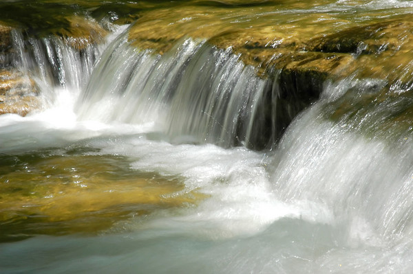 Water cascading over a waterfall on a crystal clear stream