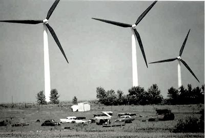 Buffalo Ridge, near Pipestone, Minnesota.  Very large wind turbines, in a very large wind farm.  I took this because of the massive size of the turbines as compared to the collection of old cars.  I also changed it to B/W on my PC, and I like this version much better.