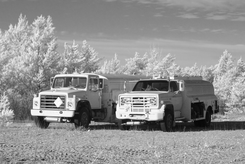 Photo taken with a Canon G5 modified to take IR photos.<br /> <br /> A boring subject but I was testing the camera while at work. Not much for grass or trees at the end of October. The evergreen trees will have to suffice. The cabs of the fuel trucks were red.
