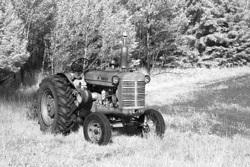 Farm tractor in Infrared. Photo taken with a Canon 10D DLSR converted to shoot IR. 1/500 second at f 5.6 and ISO 100. Very limited PS work.