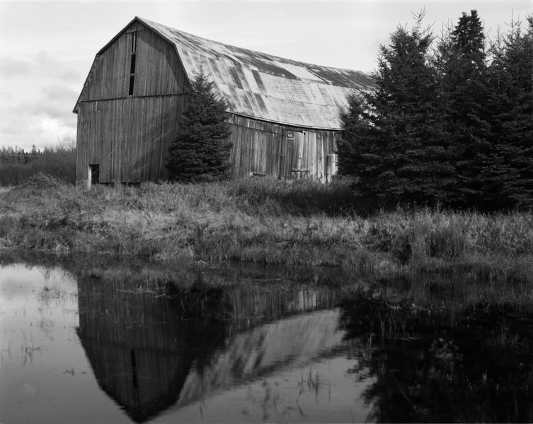 The Gamble barn. Dryden Ontario Canada.<br /> <br /> The reflection of the barn was tight against the edge of the film, but when I scanned it, the negative holder didn't allow scanning of 100% of the negative.<br /> <br /> 1/50th of a second at F11 - I think.<br /> <br /> Photo taken with a Calumet CC-400, (or CC-401 as I'm not sure which). with a Symmar 210mm F5.6. Film used was Arista EDU Ultra 100 iso 4x5 sheet film. The film was developed in a Paterson tank using a 'mod 54'. Developer used was HC-110 dilution 'B' for 5 minutes at 18.5C.
