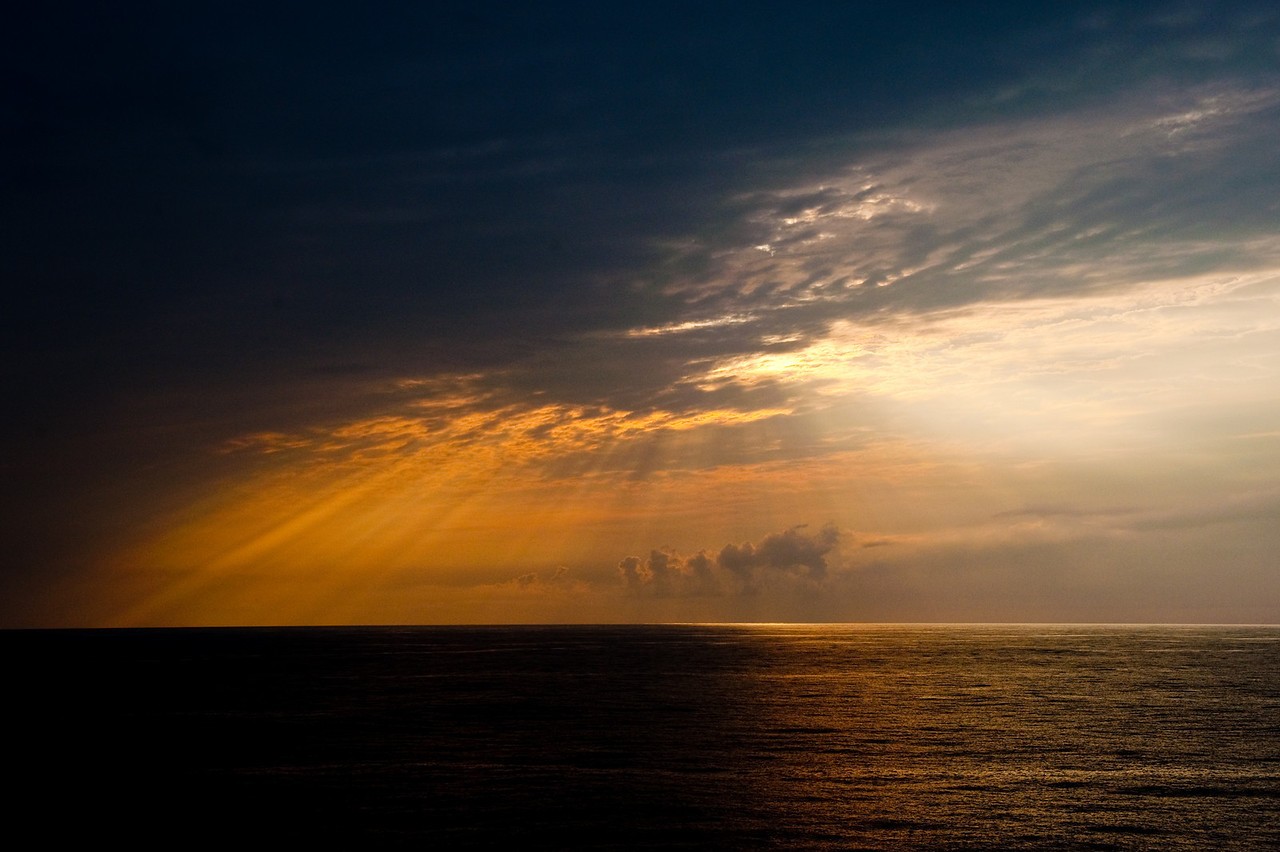 Rays of sun penetrate storm clouds near sunset in the Caribbean.