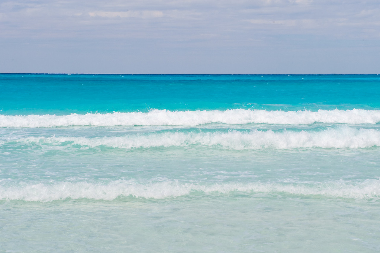 Brilliant blue water and waves breaking on a beach in the Bahamas.