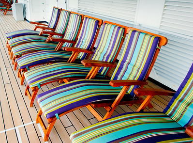 Colorful deck chairs lined up on deck of cruise ship.