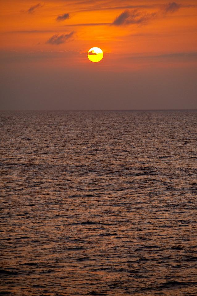 A low sun sinks into the western sky over a calm ocean.