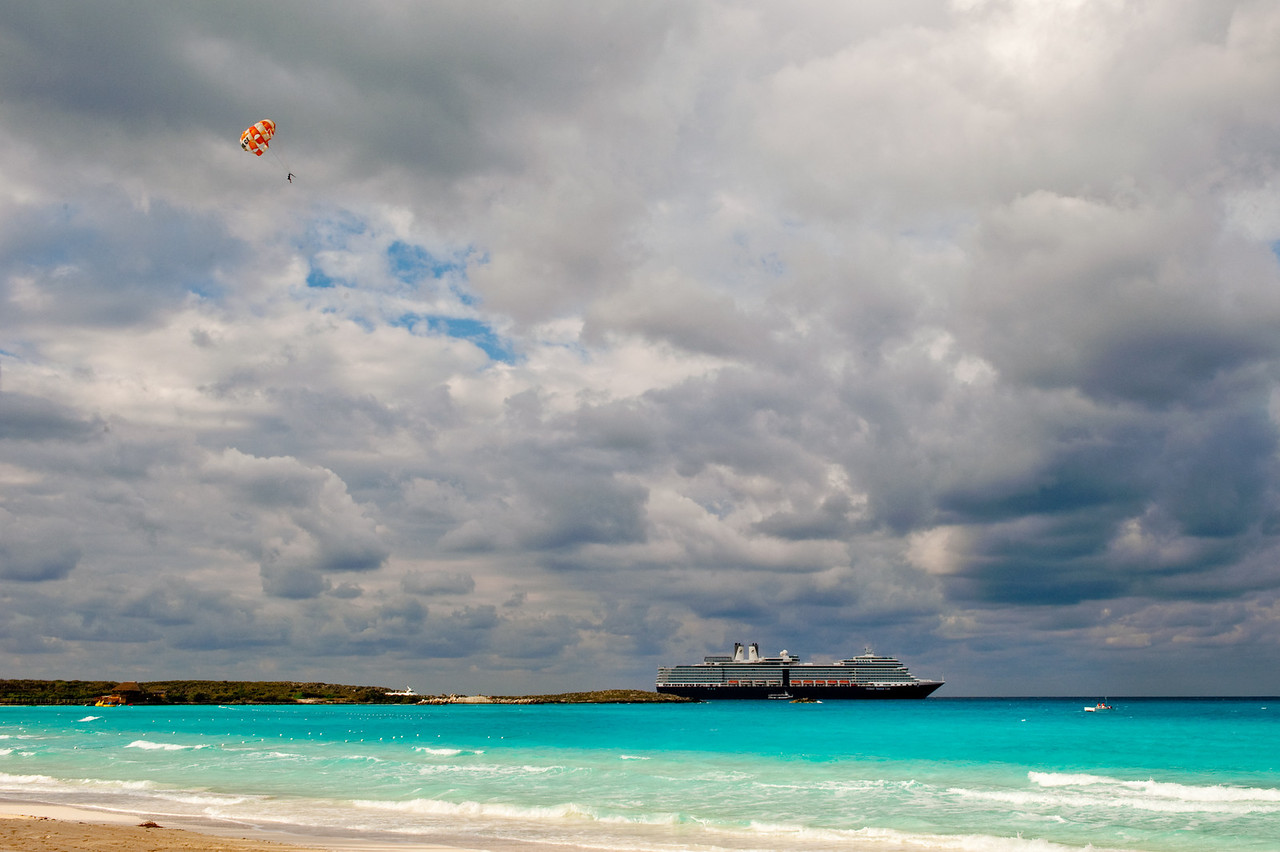Parasailing over blue waters, cruise ship in background.