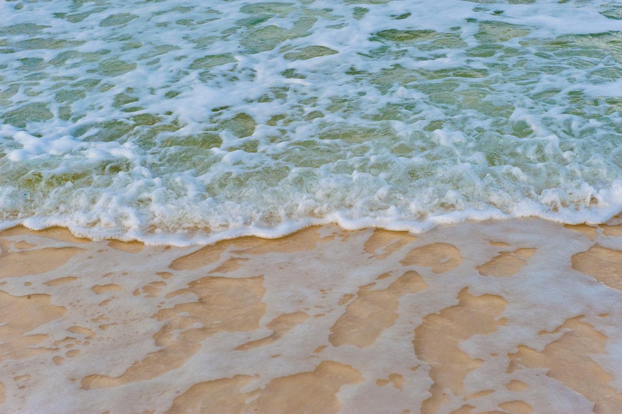 Closeup of small ocean waves over beach.