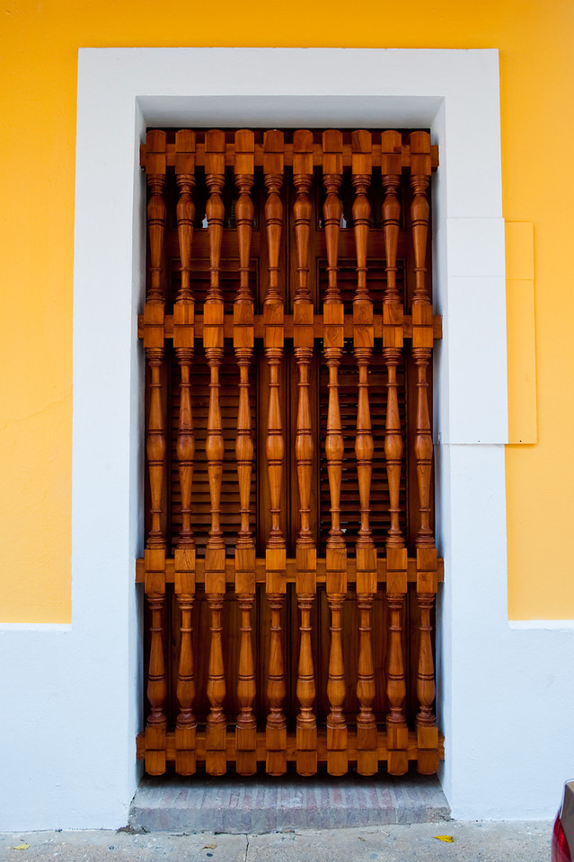Beautifully detailed wood doorway on yellow building in Old San Juan.