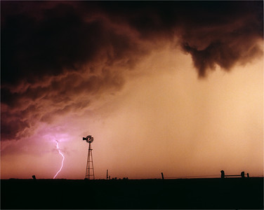 Windmill silhouetted by lightning strike from low hanging storm clouds.