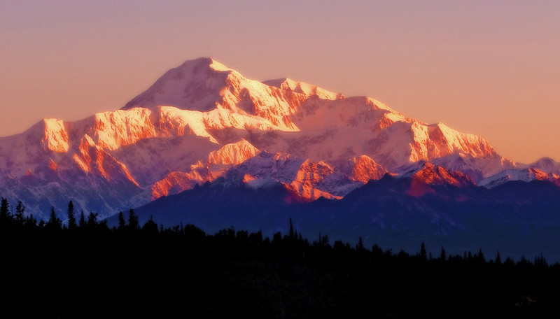 Dawn light in a rare clear sky washes over the south side of Mt. McKinley in Alaska.