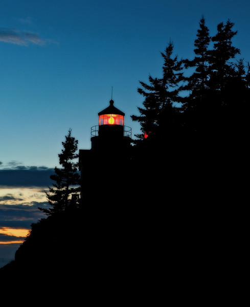 The distinctive red light of the Bass Harbor Lighthouse, just after sunset on the Maine Coast.