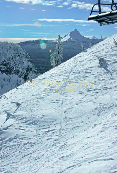 Solo ski tracks sweep down the windswept snow of Grandstand, Hoodoo Ski Area, Oregon in this scene shared by Hayrick Butte, Mt. Washington as well as the far off North and South Sisters.