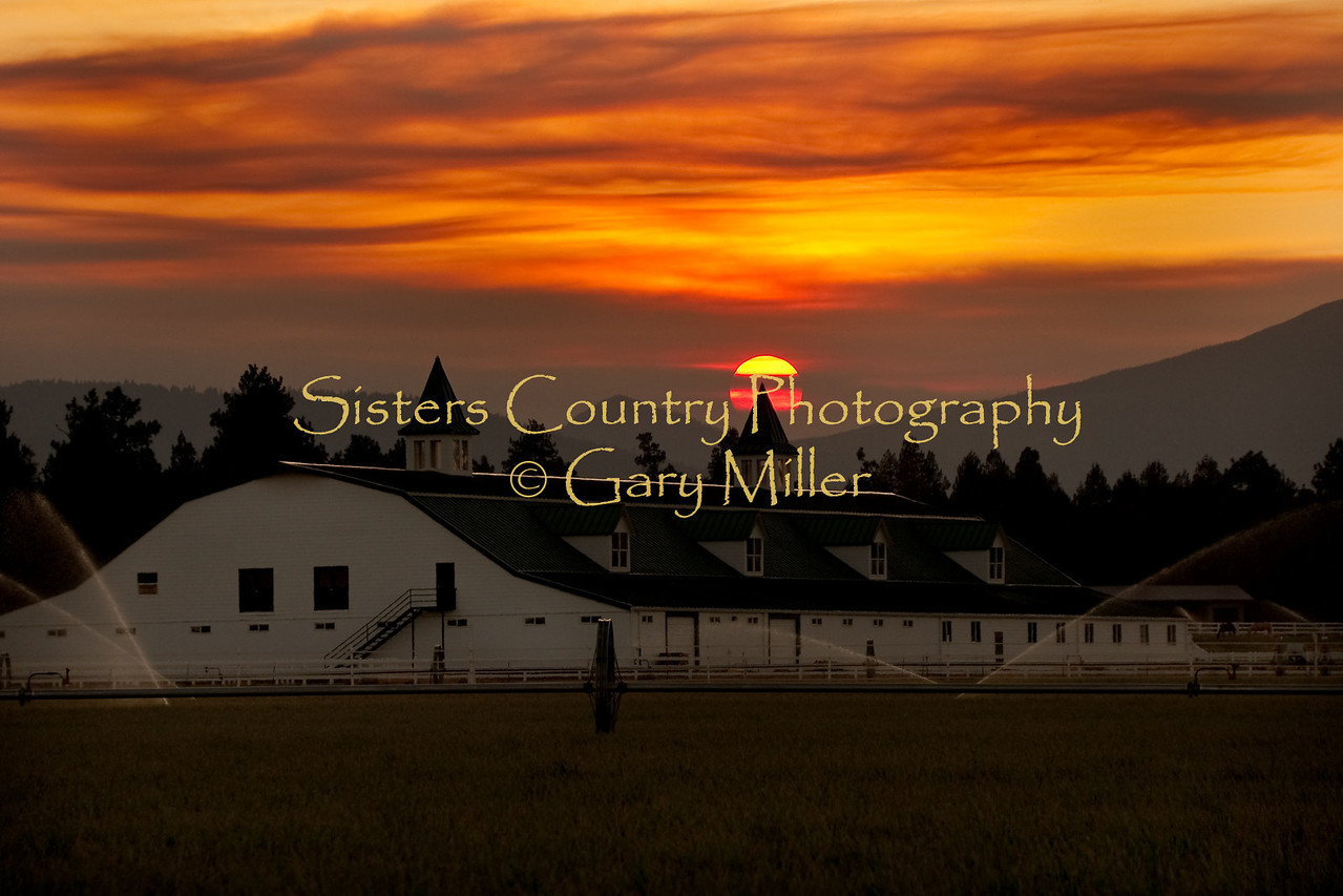 A private riding arena in Sisters, Oregon has the red orb of the sun setting on its spire. The smoke from wildland fires in the southern part of Oregon painted the sky surreal colors in Central Oregon on this day in late September 2009. Photo by Gary Miller