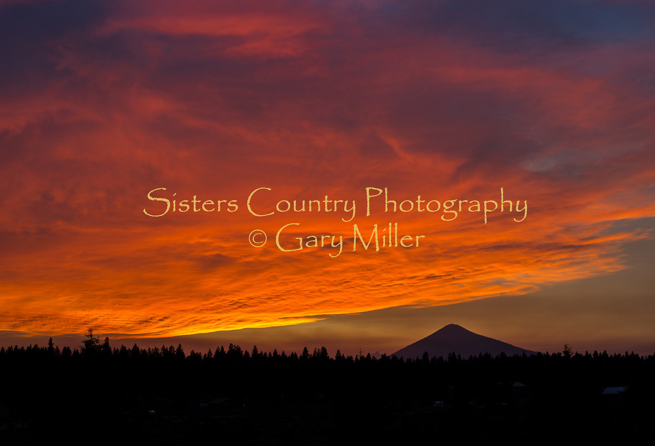 A golden Sisters Country sunset over Black Butte  as seen from the Aspen Lakes area outside of Sisters, Oregon on August 6, 2013. Smoke from the Green Ridge Fire can be seen drifting below the cloud edge. Copyright © 2013 Gary N. Miller, Sisters Country Photography