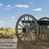 Single cannon off center right points to battlefield with blue sky and clouds behind a rock wall in Gettysburg, PA