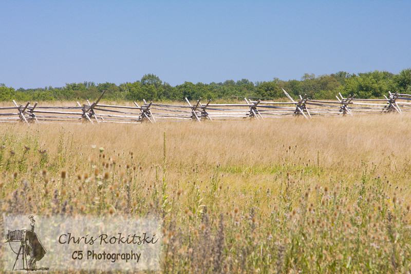 Civil war era split rail fence stretches horizontally in an open field.