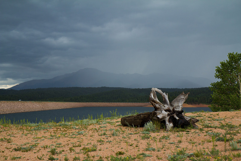 A picture taken from Rampart Reservoir. Pike's Peak is in the background and is being enveloped by a storm.