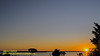 Sunset With Crescent Moon Following Far Behind In The Upper Left Hand Corner