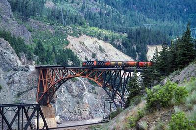 CN Eastbound unit hopper train crosses over CPR mainline and Fraser River, 1986