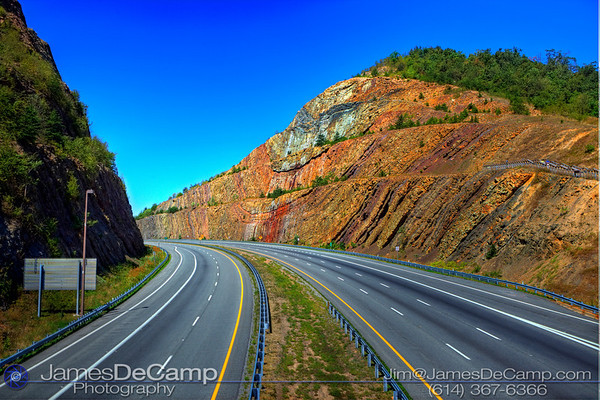 The Sideling Hill road cut along I-68 near Hancock, Maryland photographed Saturday August 28, 2010.  The geological structure is a 340 feet (100 m) deep notch excavated from the ridge of Sideling Hill for the Interstate in Washington County, Maryland. It is notable as an impressive man-made mountain pass, visible from miles away and is considered one of the best rock exposures in Maryland and the entire northeastern United States. Almost 810 feet (250 m) of strata in a tightly folded syncline are exposed in this road cut. Although other exposures may surpass Sideling Hill in either thickness of exposed strata or in quality of geologic structure, few can equal its combination of both. The rocks consist of the Devonian-Mississippian Rockwell Formation underlying the Mississippian Purslane Sandstone. An Exhibit Center to help provide the public with a better understanding of the cut's geology has been relocated to Main Street in Hancock; the exhibit area located at the westbound rest area was closed in August 2009. A pedestrian walkway bridge crosses I-68, connecting eastbound and westbound rest areas to a walkway for close-up viewing of the cut.  (© James D. DeCamp | http://www.JamesDeCamp.com | 614-367-6366)