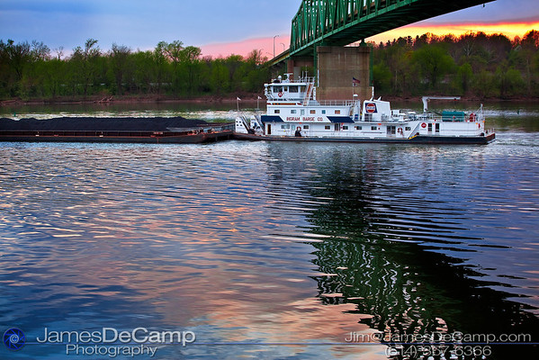 The W. H. Dickhoner tow boat, with a load of coal, makes her way downriver on the Ohio under the Route 33 Bridge just south of Ravenswood, West Virginia Wednesday evening April 7, 2010.  The W. H. Dickhoner was built in 1979 with a net tonnage of 403 Tons and is currently owned by the Ingram Marine Group.  She is powered by two GM 16-645-E7B engines, drafts 9 feet, and is 138 feet long, with a beam of 44 feet and a maximum height of 38 feet.  She was named after the past president of the Cincinnati Gas & Electric Company, William H. Dickhoner, and originally owned by the Midland Affiliated Company.  (© James D. DeCamp | http://www.JamesDeCamp.com | 614-367-6366)
