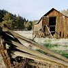 The broken fence may hold a story of why this old barn was abandoned.