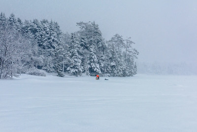 USA, Maine, Acadia National Park.  Male person in orange digging hole for ice fishing on frozen lake in a blizzard.