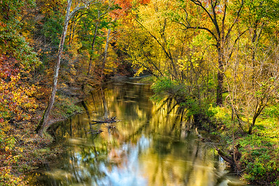 USA, Indiana.  Scenic rural landscape of trees in autumn with colorful reflections in meandering stream.