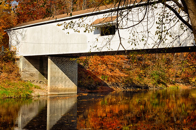 USA, Indiana.  Colorful autumn landscape of covered bridge over Wildcat Creek with reflections in rural Indiana.