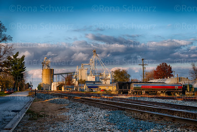 USA, Indiana. Brookston. Grainery and railroad tracks in small, Midwestern town.