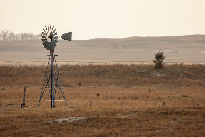 "This was taken in the sandhills north of Burwell, NE, during a deer hunting trip in 2009.  To me, this photograph conveys the unique isolation of the area.  There is something about the vastness of the space that makes a simple item, such as a windmill or a tree, compelling.  This shot is a ""soft"" because of the combination of high ISO (high for my old camera), long zoom, slow shutter speed and no tripod.  Even though soft, I've printed it at 12x18 and like the results."