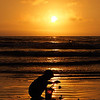 Child Playing with Pail on Seashore Silhouetted by Setting Sun