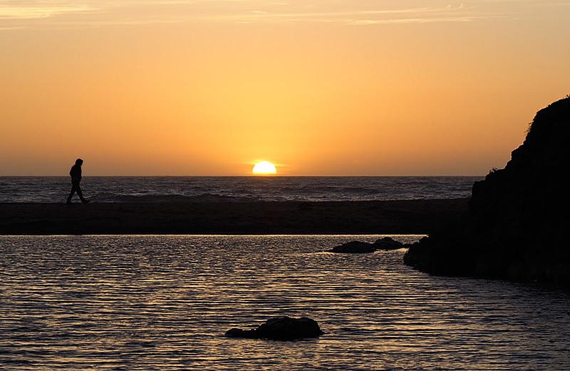 Man Walking on Beach at Sunset