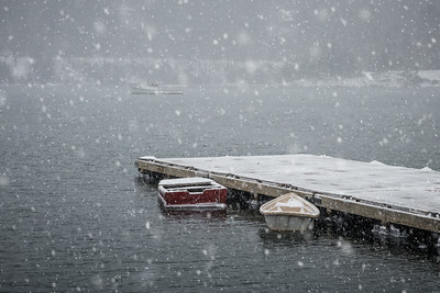 USA, Maine.  Row boats and fishing boat in harbor during heavy snow storm at Acadia National Park.