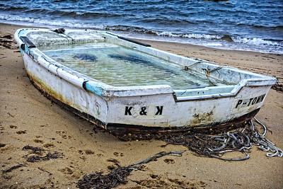 USA, Provincetown, MA.  A water-filled dory on the sand at the beach