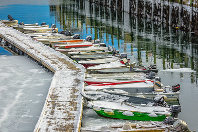 Acadia National Park, Maine, USA.  motor boats lined at pier up in winter with reflections in water.