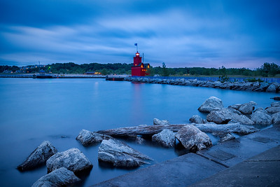 Holland, Michigan, USA.  Long exposure of Big Red Lighthouse with silky water and rocks in the foreground at twilight.