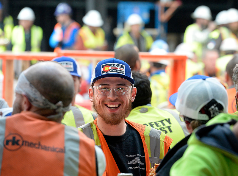Sporting his new Scheels hat, given only to contractors who have worked on the building, Alex Gomez, center, an employee with RKMI, shares a laugh with co-workers during lunch Wednesday, March 1, 2017, at the new Scheels store at the 2534 development in Johnstown.  (Photo by Jenny Sparks/Loveland Reporter-Herald)