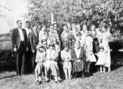 "From Terri Vogel Kelly (a distant cousin): ""Names to faces: From left (back row): Clinton Creed Robbins, Benjamin Anderson Robbins, unknown man, my grandma Ruth Robbins Vogel, one of her older sisters (and spouse behind her), another older sister, my grandpa Clarence Vogel behind her, then Dale Vogel (being held by Uncle Roy Workman), then Ethel Robbins Workman, then known couple and their children. Not sure who is in front, except one of the smaller girls must be Betty Vogel (Dale's sister, who is 3 years older than him) and of course, Lucy Lodena Eads Robbins. This picture then must have been taken around 1932. Dena Robbins died in 1934, and Dale was born in 1930. My Dad, Dale, has confirmed the ones he knows from this photo.""; ""Update from my Dad: 3 of the little girls would be his sister Betty Vogel, who was around 5, and his cousins Pearl Workman (about 10) and Elsie Workman (around 12). He is the 2 year old in the back sucking his thumb (looks just like my brother at that age!). He's just not sure which of the girls is which."""