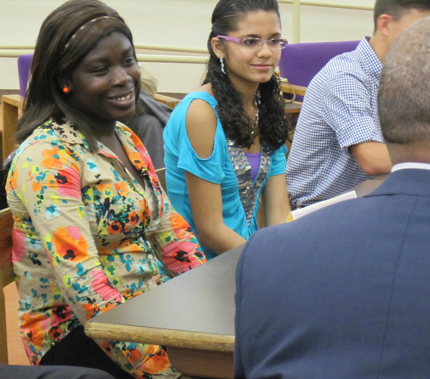 . Pittsfield High School seniors Christine Ahoussi (left) and Gladys Garcia (right) smile while chatting with Gov. Deval Patrick during a student forum held Monday at the school with state and local officials. Jenn Smith/Berkshire Eagle Staff Monday, Oct. 7, 2013