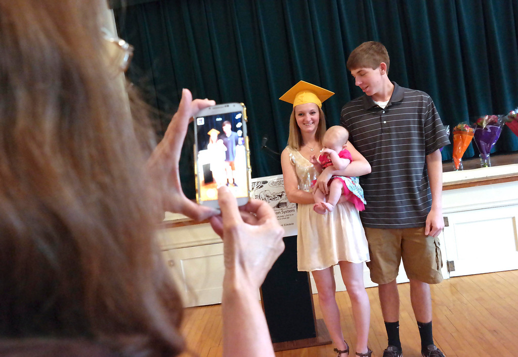 . Mary Tart (holding camera) takes a picture of her daughter Alexys Tart, holding her baby Emma Walton with Emma\'s father Brandon Walton at the Helen Berube Teen Parenting Program Commencement, Friday June 6, 2014.  Ben Garver / Berkshire Eagle Staff / photos.berkshireeagle.com