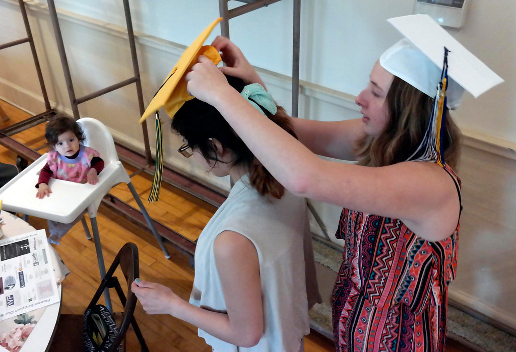 . Baby hailey Van Rumund watches Krystal Ferrari put a graduation cap on her mother Ashley Reyes at the Teen Parent Program commencement in Pittsfield. Friday June 6, 2014.  Ben Garver / Berkshire Eagle Staff / photos.berkshireeagle.com