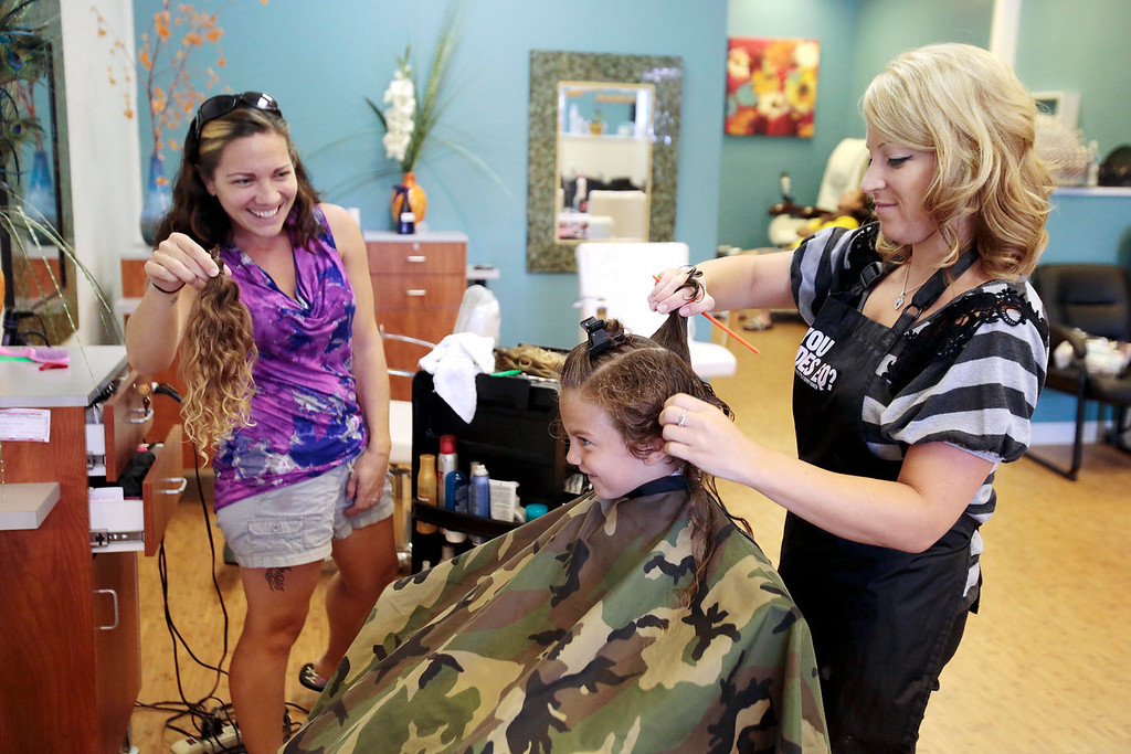 . Sarah DeJesus shows her son Kingston 5, the 15 inches of hair that he will be donating to Wigs for Kids, as he gets his first haircut from Bre Calkins at Split Ends Hair Salon in Pittsfield. Saturday, August 3, 2013. Stephanie Zollshan/Berkshire Eagle Staff.