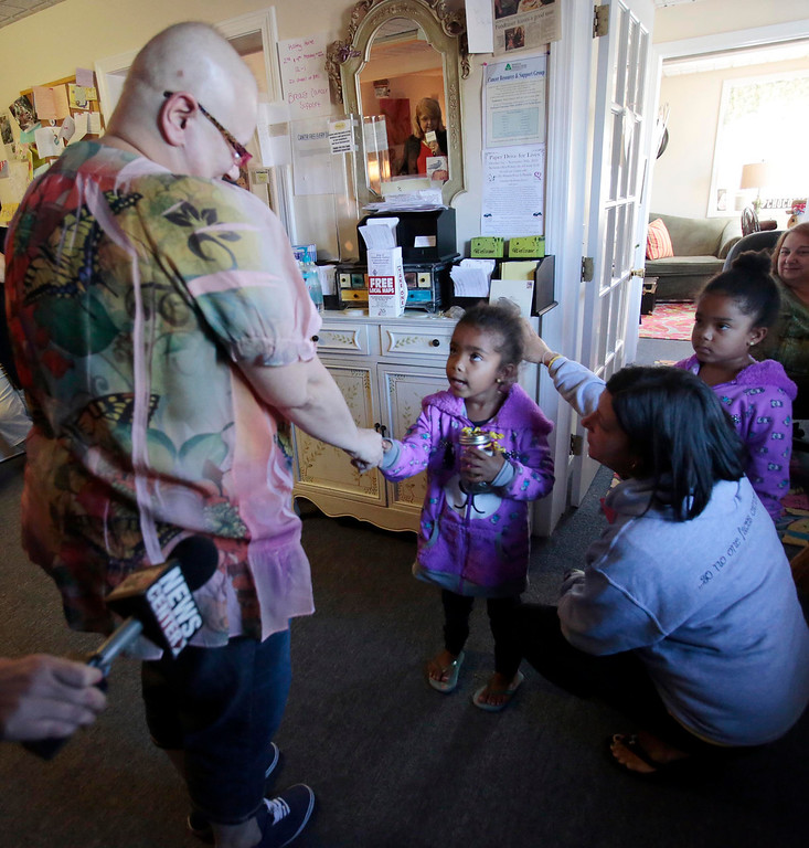 . Four-year-old twins Emma, center, and Eva Msibi meet Sharon Debonis, a cancer victim and recipient of the proceeds from their lemonade stand at Moments House in Pittsfield. Monday, September 23, 2013. Stephanie Zollshan/Berkshire Eagle Staff.