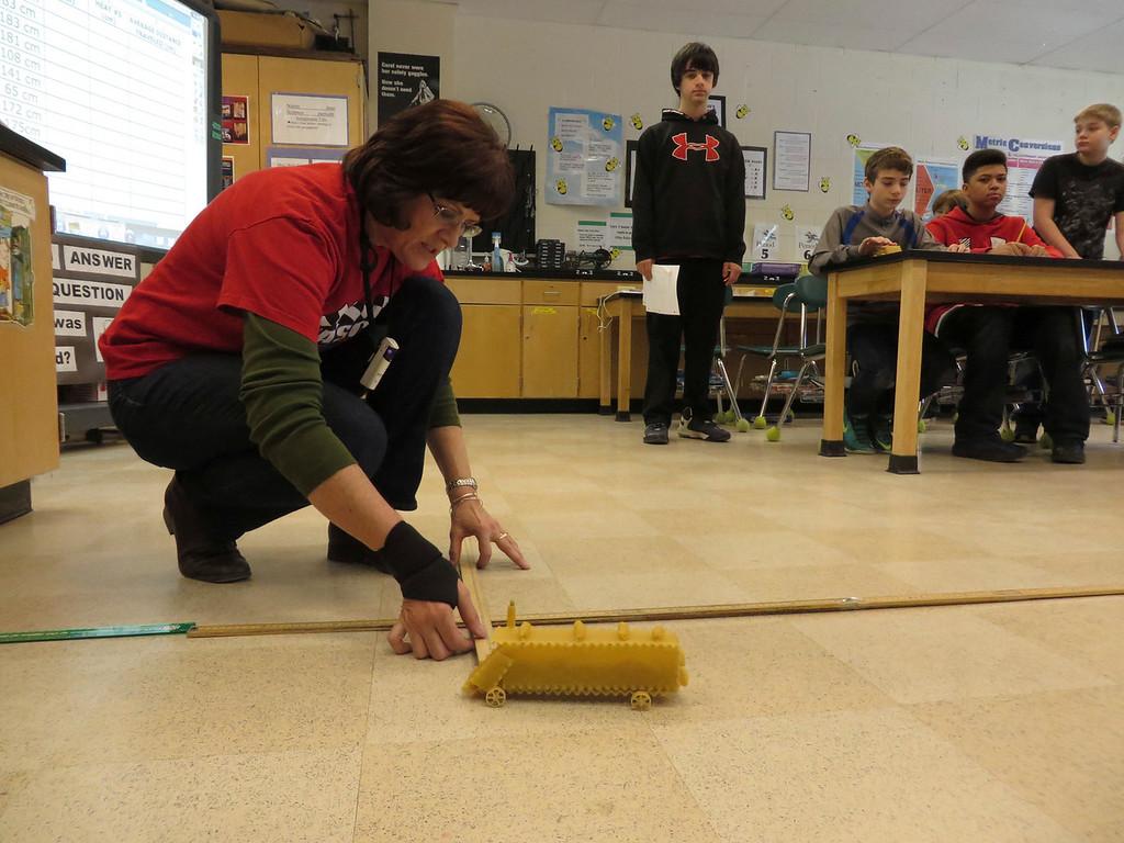 ". Herberg Middle School seventh-grade science teacher Ellen Lantz measure the distance that a \""pasta pod\"" raced as part of a physics lesson. Jenn Smith/Berkshire Eagle Staff/ photos.berkshireeagle.com Friday, March 7, 2014"