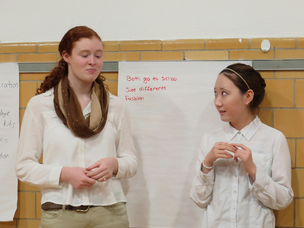 . St. Joseph Central High School exchange student Jay Lee (right), 17, watches as her classmate Clarissa Mitchell, 17, tries a chocolate-covered soybean during a cultural workshop presented on North and South Korea. Jenn Smith/Berkshire Eagle Staff Friday, March 16, 2014