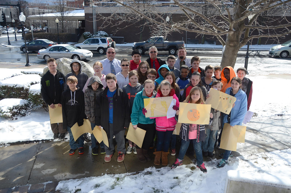 . Sullivan School students in Jim Holmes\' sixth grade class met with Mayor Richard Alcombright, to give him a Earth Day poster, one of a dozen they made, and then continued on giving them to local businesses to display in their storefronts in downtown North Adams on Wednesday, April, 16, 2014. Students pose with their posters and the Mayor in front of City Hall. Gillian Jones / Berkshire Eagle Staff / photos.berkshireeagle.com