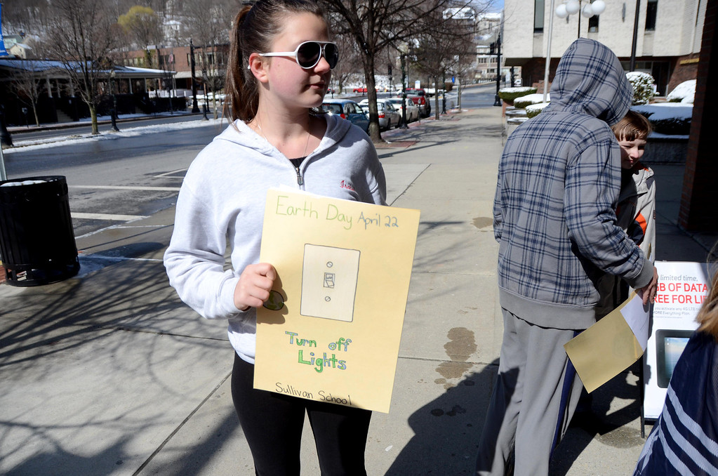 . Sullivan School student Isabel Lescarbeau, 12, holds up an Earth Day poster that she made in Jim Holmes\' sixth grade class. Students gave them to local businesses to display in their storefronts in downtown North Adams on Wednesday, April, 16, 2014. Gillian Jones / Berkshire Eagle Staff / photos.berkshireeagle.com