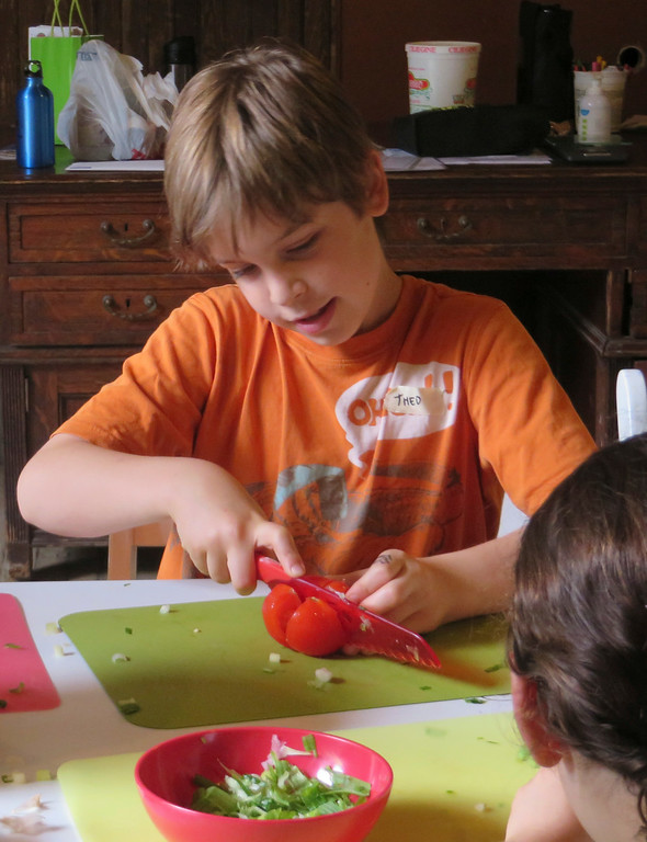 . Theo Maurino, 10, of Lenox tries his hand at cutting a tomato \'blossom\' during The Nutrition Center\'s Food Adventures summer camp held last week at The Mount in Lenox. Jenn Smith/Berkshire Eagle Staff/photos.berkshireeagle.com Thursday, July 3, 2014